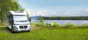RV parked by a lake with a campsite - RV LOANS
